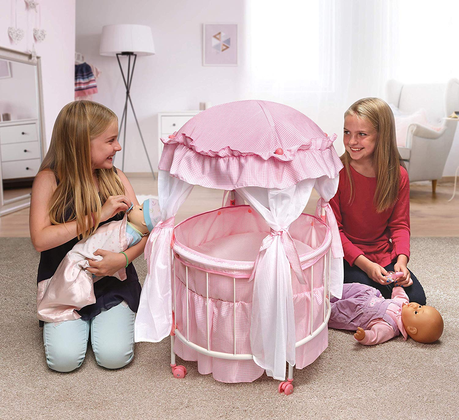 This pink-and-white gingham-decorated steel-metal-and-plastic round crib that comes complete with inner liner, padded mat